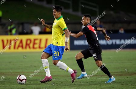 Brazil's Roberto Firmino, left, dribbles past Peru's Yoshimar Yotun during the second half of an international friendly soccer match, in Los Angeles