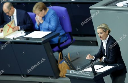 Alice Weidel, co-faction leader of the Alternative for Germany party, delivers a speech during a meeting of the German federal parliament, Bundestag, at the Reichstag building in Berlin, Germany, . In the background are German Finance Minister Olaf Scholz, left, and German Chancellor Angela Merkel, right