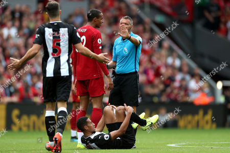 Referee Andre Marriner speaks with Joel Matip of Liverpool