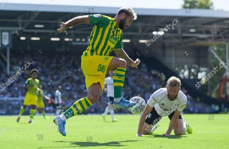 Charlie Austin of West Bromwich Albion controls the ball after fouling Tim Ream of Fulham