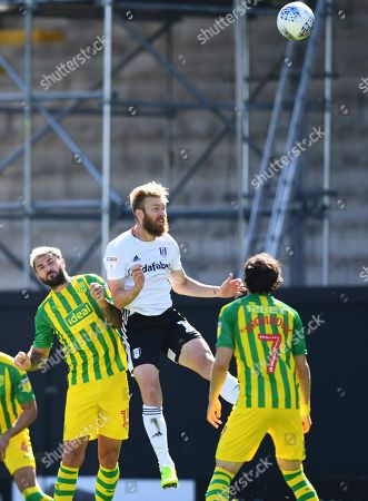 Tim Ream of Fulham heads under pressure from Charlie Austin of West Bromwich Albion