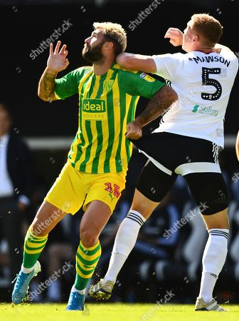 Charlie Austin of West Bromwich Albion grabs the shorts of Alfie Mawson of Fulham