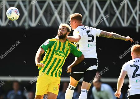 Alfie Mawson of Fulham heads under pressure from Charlie Austin of West Bromwich Albion