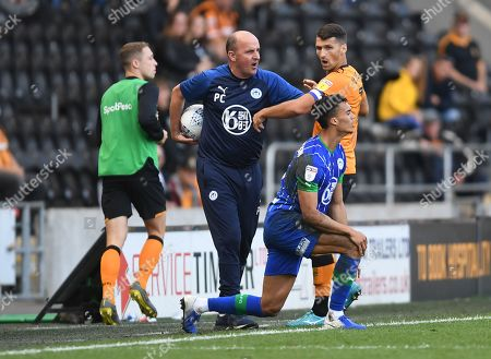 Eric Lichaj of Hull City tries to get the ball from Paul Cook manager of Wigan Athletic on the touchline