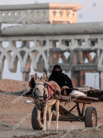 A Palestinian elderly woman rides her donkey cart near a destroyed Yasser Arafat airport buildings in the east Rafah, southern Gaza Strip, 11 September 2019. The Yasser Arafat airport, opened in November 1998, is not operational since December 2001 after the facility buildings were targeted by Israeli airstrikes, while runway was damaged by Israeli bulldozers in 2002.