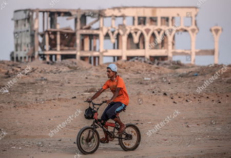 A Palestinian child rides his bicycle near destroyed Yasser Arafat airport buildings in the east Rafah, southern Gaza Strip, 11 September 2019. The Yasser Arafat airport, opened in November 1998, is not operational since December 2001 after the facility buildings were targeted by Israeli airstrikes, while runway was damaged by Israeli bulldozers in 2002.