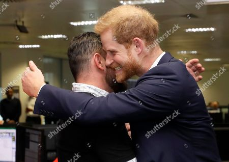 Prince Harry hugs former Invictus Games competitor Paul Vince as he attends the 15th annual BGC Charity Day