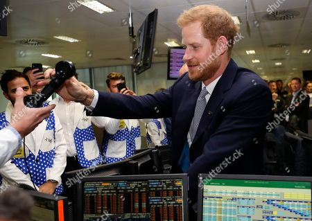 Prince Harry is handed a phone as he attends the 15th annual BGC Charity Day
