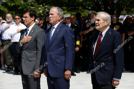 """George W. Bush, Donald Rumsfeld, Mark Esper. Defense Secretary Mark Esper, from left, former President George W. Bush and former Defense Secretary Donald Rumsfeld pause during the playing of """"Taps"""" after Bush placed a wreath on the grounds of the National 9/11 Pentagon Memorial at the Pentagon in Washington, in observance of the 18th anniversary of the September 11th attacks"""
