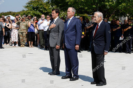George W. Bush, Donald Rumsfeld, Mark Esper. Defense Secretary Mark Esper, from left, former President George W. Bush and former Defense Secretary Donald Rumsfeld pause during a rendition of Taps after Bush placed a wreath on the grounds of the National 9/11 Pentagon Memorial at the Pentagon in Washington, in observance of the 18th anniversary of the September 11th attacks