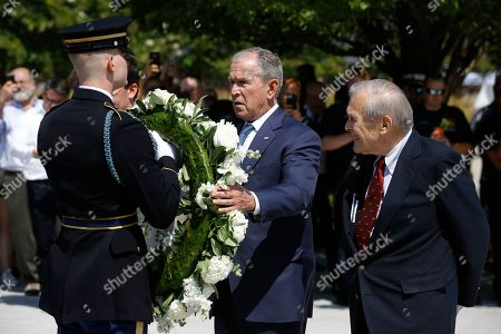 George W. Bush, Donald Rumsfeld. Former President George W. Bush places a wreath as former Defense Secretary Donald Rumsfeld, right, watches, on the grounds of the National 9/11 Pentagon Memorial at the Pentagon in Washington, in observance of the 18th anniversary of the September 11th attacks
