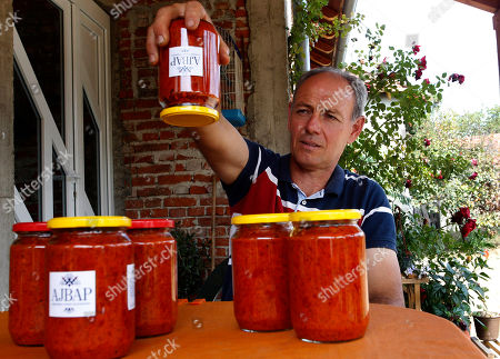 Stock Image of Stevica Markovic holds a jar of traditional Serbian specialty Ajvar in the village of Brestovac, 30 km south of Nis, Serbia, 11 September 2019. Ajvar is a pepper-based condiment made from red bell peppers and oil. Ajvar is used in the Balkans especially in Serbia, where is homemade Ajvar made of roasted peppers. The Markovic family grows this special pepper on their property and every September they make Ajvar by hand in the traditional way.