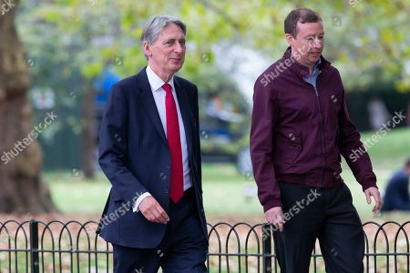 MP for Runnymede Philip Hammond (l) walks in St James?s Park.