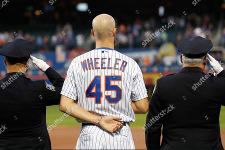 New York Mets pitcher Zack Wheeler (45) stands between two uniformed officers during a Sept. 11, 2001. tribute before the team's baseball game against the Arizona Diamondbacks, in New York