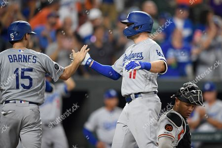 Stock Photo of Los Angeles Dodgers' A.J. Pollock celebrates his two-run with Austin Barnes (15) during the sixth inning of a baseball game as Baltimore Orioles catcher Pedro Severino kneels at right, in Baltimore