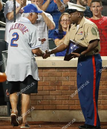 Stock Photo of Former New York Mets manager Bobby Valentine, left, greets a serviceman who was honored during a baseball game against the Arizona Diamondbacks, in New York