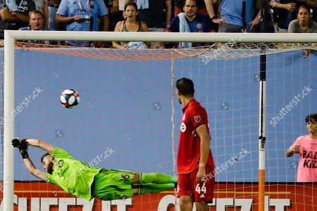 Toronto FC goalkeeper Quentin Westberg (16) deflects a shot on goal by New York City FC's Ronald Matarrita as teammate Omar Gonzalez (44) and fans watch during the second half of an MLS soccer match, in New York. The game ended in a 1-1 draw