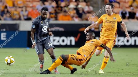 Houston Dynamo midfielder Oscar Garcia, middle, slides to kick the ball away from Minnesota United defender Romain Metanire (19) as Dynamo midfielder Thomas McNamara, right, watches during the first half of an MLS soccer match, in Houston