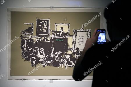 A visitor takes a photo of an art work by Banksy during a media preview of The Art Of Banksy at Moore Park's Entertainment Quarter in Sydney, Australia, 12 September 2019. The Art Of Banksy, the world's largest touring collection of Banksy's works, will open in Sydney on 13 September and is curated by Banksy's former manager and photographer Steve Lazarides.