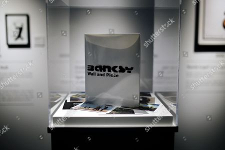 An art book by Banksy, titled Wall And Piece, is displayed during a media preview of The Art Of Banksy at Moore Park's Entertainment Quarter in Sydney, Australia, 12 September 2019. The Art Of Banksy, the world's largest touring collection of Banksy's works, will open in Sydney on 13 September and is curated by Banksy's former manager and photographer Steve Lazarides.