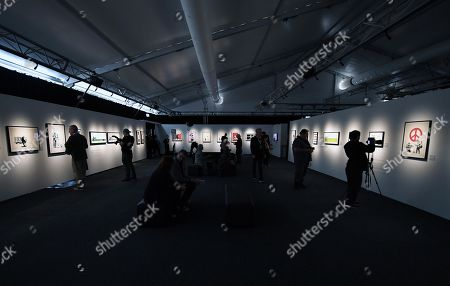 Stock Picture of Visitors look at art work by Banksy is displayed during a media preview of The Art Of Banksy at Moore Park's Entertainment Quarter in Sydney, Australia, 12 September 2019. The Art Of Banksy, the world's largest touring collection of Banksy's works, will open in Sydney on 13 September and is curated by Banksy's former manager and photographer Steve Lazarides.
