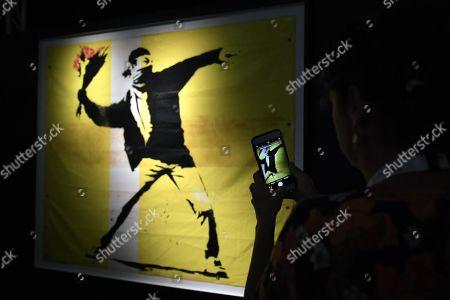 A visitor take a photo of an art work by Banksy is displayed during a media preview of The Art Of Banksy at Moore Park's Entertainment Quarter in Sydney, Australia, 12 September 2019. The Art Of Banksy, the world's largest touring collection of Banksy's works, will open in Sydney on 13 September and is curated by Banksy's former manager and photographer Steve Lazarides.