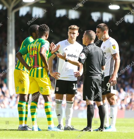 Referee David Webb speaks with players from both teams