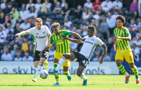 Grady Diangana of West Bromich Albion with Steven Sessegnon and Harrison Reed of Fulham challenging