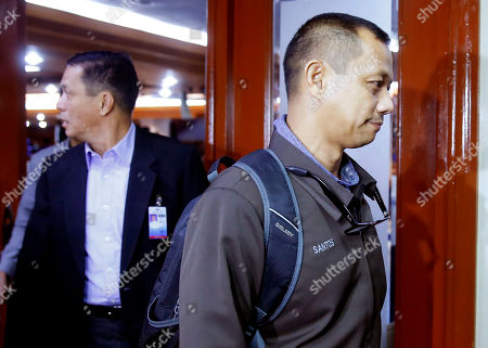 Bureau of Corrections official Fredrick Anthony Santos, right, is escorted to his detention after he and two other officials were cited in-contempt in the continuing Philippine Senate probe, in suburban Pasay city south of Manila, Philippines, on the failed release of former Mayor Antonio Sanchez who was convicted in the 1993 rape and murders of two students. The Senate probe has uncovered alleged anomalies and corruption over the release of hundreds of prisoners, including convicted rapists and drug traffickers, through a law rewarding good behavior in detention