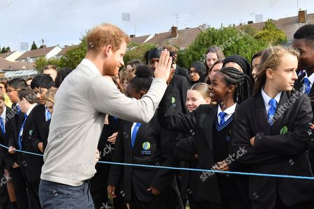 Prince Harry gives a high 5 to Dinnae Bartlett as he visits Lealands High School as part of the Rugby Football Union (RFU) All Schools programme