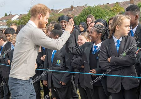 Stock Picture of Prince Harry gives a high 5 to Dinnae Bartlett as he visits Lealands High School as part of the Rugby Football Union (RFU) All Schools programme