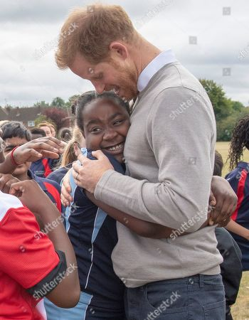 Prince Harry gets a hug from Zara Jess Gudza as he visits Lealands High School as part of the Rugby Football Union (RFU) All Schools programme
