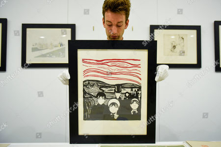 """A technician presents a lithograph by Edvard Munch at a photocall for """"Les Peintres-Graveurs"""", a multi-artist portfolio of lithographs published in 1896 by Ambroise Vollard, to be auctioned at Sotheby's on September 17 with an estimate of £500,000 to £1,000,000. It is the only known complete example and includes 22 prints by the greatest Impressionist and Post-Impressionist artists such as Pierre Bonnard, Odilon Redon, Théo van Rysselberghe, Auguste Renoir, and Edouard Vuillard., as well as the first colour lithograph by a then not so well-known Edvard Munch."""