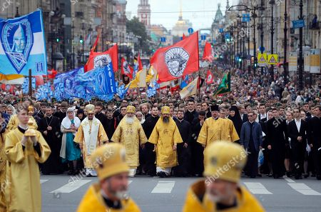 Stock Image of Orthodox believers walk behind clergy as they take part in a procession along Nevsky Prospect to mark the anniversary of the Alexander Nevsky Monastery in St.Petersburg, Russia, . Russian Orthodox faithful commemorate the date of September 12, 1724, when Russian Tsar Peter The Great transferred the relics of prince Alexander Nevsky from town of Vladimir to St.Petersburg, the new capital of Russia