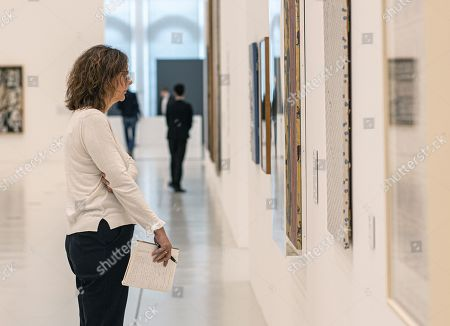 Stock Image of A visitor looks at artworks in the exhibition 'Die jungen Jahre der alten Meister' (The Early Years of the Old Masters) in the Deichtorhallen venue in Hamburg, Germany, 12 September 2019. The exhibition featuring German famous painters Georg Baselitz, Gerhard Richter, Sigmar Polke, and Anselm Kiefer runs from 13 September to 05 January 2020.