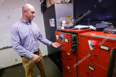 Barberton narcotics detective Ben Hill looks over file cabinets with stored narcotics evidence at the department headquarters, in Barberton, Ohio