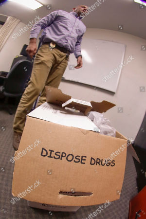 Stock Photo of Barberton narcotics detective Ben Hill shows a box of stored drugs before they are disposed of at the department headquarters, in Barberton, Ohio