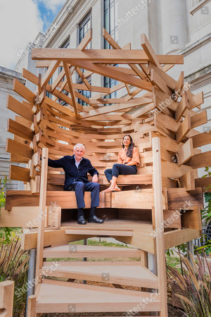 Stock Image of Sir John Sorrell CBE, Chairman of London Design Festival, commissioned Juliet Quintero (both pictured) of Dallas-Pierce-Quintero, to create a lookout seat for the garden. It is shaped like a bird's nest and will create a space for contemplation and reflection. The planks of red oak were thermally modified to make the piece more durable for outdoor use and the piece was structurally engineered by Arup. Sir John invited leaders of London's cultural institutions to collaborate with some of Europe's most exciting designers to create a 'legacy' piece of design in American red oak for London Design Festival. The pieces ' ten in total ' are on show in the Sculpture Gallery of the Victoria & Albert Museum, with only this one outside the Natural History Museum on Exhibition Road - they will be in place for the duration of London Design Festival, 14-22 September 2019. The project is in collaboration with the American Hardwood Export Council (AHEC).