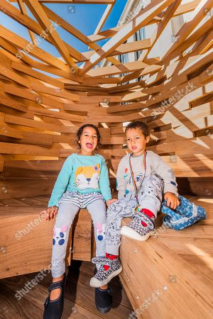 A couple of visiting kids are the first members of the public to enjoy the seat - Sir John Sorrell CBE, Chairman of London Design Festival, commissioned Juliet Quintero of Dallas-Pierce-Quintero, to create a lookout seat for the garden. It is shaped like a bird's nest and will create a space for contemplation and reflection.  The planks of red oak were thermally modified to make the piece more durable for outdoor use and the piece was structurally engineered by Arup. Sir John invited leaders of London's cultural institutions to collaborate with some of Europe's most exciting designers to create a 'legacy' piece of design  in American red oak for London Design Festival. The pieces ' ten in total ' are on show in the Sculpture Gallery of the Victoria & Albert Museum, with only this one outside the Natural History Museum on Exhibition Road - they will be in place for the duration of London Design Festival, 14-22 September 2019. The project is in collaboration with the American Hardwood Export Council (AHEC).