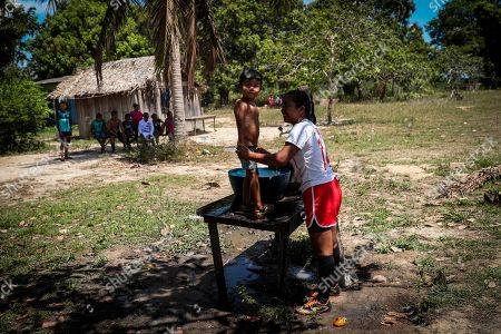 A player of 'Bayern Munich' with her son at the Marmelos village, Amazon, Brazil, 10 September 2019 (issued 12 September 2019). The village attends from 8am and until the end of the afternoon a tournament between the male and female teams of different communities from the Tenharim indigenous reserve. They wear fake uniforms of Borussia Dortmund, Paris Saint-Germain, Bayern Munich, Manchester City or Schalke 04, sold by peddlers at a near city. It's the Amazon's 'Champions League', but with goals made of dry palm. Young indigenous see in soccer a ball of oxygen amid the fires that consume the region.