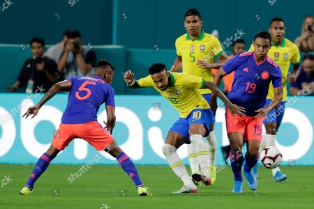 Stock Picture of Brazil forward Neymar Jr (10) kicks the ball as Colombia midfielder Wilmar Barrios (5) and forward Luis Muriel (19) defend during the first half of a friendly soccer match, in Miami Gardens, Fla