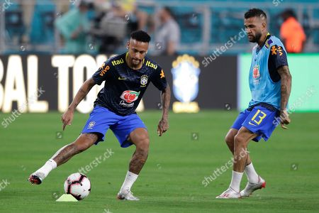 Brazil forward Neymar Jr, left, and defender Daniel Alves (13) warm up before a friendly soccer match against Colombia, in Miami Gardens, Fla