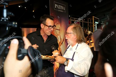 Renowned chief and founder of Patina Restaurant Group Joachim Splichal, right, is interviewed about his special menu of classic dishes and small plates created for the 71st Emmy Awards Governors Ball at the press preview, in Los Angeles