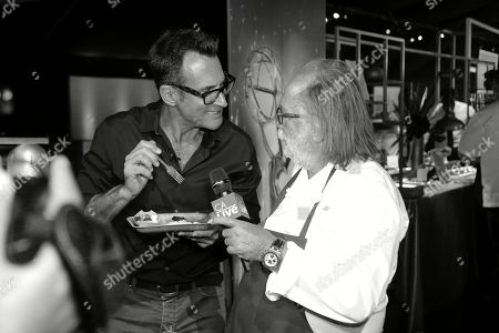 Stock Picture of Renowned chief and founder of Patina Restaurant Group Joachim Splichal, right, is interviewed about his special menu of classic dishes and small plates created for the 71st Emmy Awards Governors Ball at the press preview, in Los Angeles