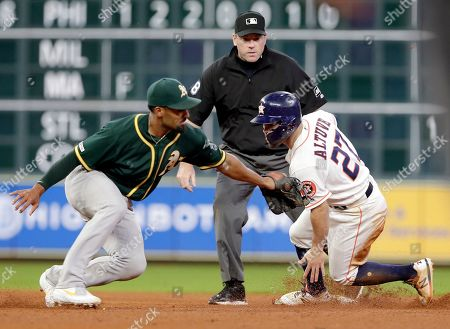 Houston Astros second baseman Jose Altuve (27) is safe at second base on a steal as Oakland Athletics shortstop Marcus Semien, left, attempts a tag with an empty glove as umpire Chris Conroy looks on during the sixth inning of a baseball game, in Houston