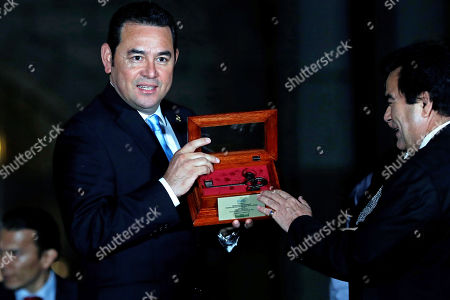 Guatemalan President Jimmy Morales (L) receives the key for National Palace of Culture at the historical center of Guatemala City, Guatemala, 12 September 2019. Morales was attending an event at the National Palace of Culture when a group of demonstrators interupted, protesting against the removal of 41 crosses at a nearby square that comemorated the death 41 girls on 08 March 2017.