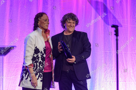 Stock Image of Lonnie Ali, Michael Lang. Lonnie Ali, Co-Founder of the Muhammad Ali Center and wife of Muhammad Ali, left, presents music icon Michael Lang, best known for co-creating and producing the original 1969 Woodstock Festival, with the Lifetime Achievement Award for using music to spread a universal message of unity and peace during the 7th annual Muhammad Ali Humanitarian Awards at the Louisville Marriott Downtown, in Louisville, Ky