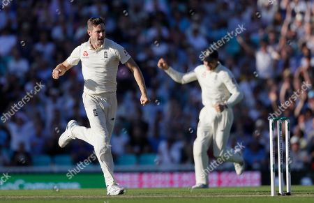 England's Chris Woakes celebrates taking the wicket of Australia's Steve Smith during the second day of the fifth Ashes test match between England and Australia at the Oval cricket ground in London