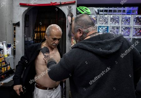 Turkish retiree Cahit Yilmaz (L) shows his tattoo portrait of the founder of modern Turkey Mustafa Kemal Ataturk, symbolizing secularism, in Istanbul, Turkey, 13 May 2019. Yilmaz calls himself a social democrat. Turkey, a historically secular state, has undergone dramatic political changes in recent years, as President Erdogan, backed by a conservative Muslim and largely rural base, has tightened his grip on power. Multiple elections, constitutional referendums and massive popular protests based in Gezi Park and Taksim Square in 2014 have created a new generation of increasingly politicized Turks, especially in the capital city, Istanbul. These changes are reflected in popular culture, and political symbols and icons have become more prominent in the public sphere. This is also true for body art, with Turkish tattoo artists saying that the demand for political tattoos has also increased in recent years.