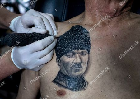 A tattoo artist works on Turkish retiree Cahit Yilmaz's tattoo portrait of the founder of modern Turkey Mustafa Kemal Ataturk, symbolizing secularism, in Istanbul, Turkey, 13 May 2019. Yilmaz calls himself a social democrat. Turkey, a historically secular state, has undergone dramatic political changes in recent years, as President Erdogan, backed by a conservative Muslim and largely rural base, has tightened his grip on power. Multiple elections, constitutional referendums and massive popular protests based in Gezi Park and Taksim Square in 2014 have created a new generation of increasingly politicized Turks, especially in the capital city, Istanbul. These changes are reflected in popular culture, and political symbols and icons have become more prominent in the public sphere. This is also true for body art, with Turkish tattoo artists saying that the demand for political tattoos has also increased in recent years.